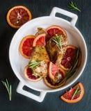 Coscie di pollo arrostite sulle fette di arance rosse nel piatto bianco di cottura Annerisca la priorità bassa dell'ardesia Fotografie Stock