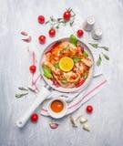 Coscie di pollo con la marinata, le erbe e le spezie rosse del peperoncino rosso in pentola bianca su fondo di legno blu Fotografia Stock