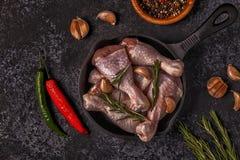 Coscie di pollo crude con i rosmarini, l'aglio ed i peperoncini rossi Immagine Stock