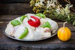 Coscie di pollo crude su un vassoio con pepe e basilico roventi Priorità bassa di legno Primo piano Immagine Stock
