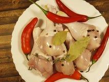 Coscie di pollo crude un di legno, conteggio su placchetta di nutrizione della preparazione della spezia della cucina della carne Immagine Stock