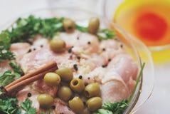 Coscie di pollo, prezzemolo, cannella e spezie crudi in piatto di vetro sulla tavola bianca, fine su Fotografie Stock