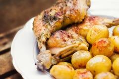 Coscie di pollo servite con le patate del bambino Immagini Stock
