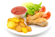 Coscie di pollo su un piatto bianco con le fette di pomodoro e lattuga e patate fritte e ketchup su fondo bianco Immagine Stock