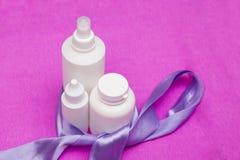 Coscosmetic在桃红色背景设置了 白色医疗瓶 白色塑料瓶 三个小白色瓶 免版税库存图片