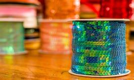 Cose acima dos rolos brilhantes da fita colorida do verde das lantejoulas, multi-coloridos sobre uma tabela de madeira em um fund Imagens de Stock