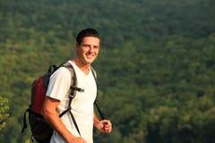 Cose para arriba del hombre sonriente con la mochila en backgound de la naturaleza Fotografía de archivo