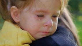 Close-up portrait of beautiful little two-year-old girl crying in mother`s arms. Close-up portrait of a beautiful little two-year-old girl crying in her mother`s stock video footage