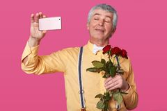 Cose up portrait of handsome senior man making selfie before dating, looks smiling at camera, wears yellow shirt with suspenders royalty free stock photography
