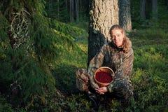 Cosecha Cowberrys de la mujer joven. Foto de archivo