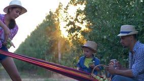 Cosecha de la fruta, familia feliz de jardineros que se relajan en la hamaca en jardín de la manzana metrajes