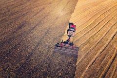 Cosecha de la cosecha mecánica de la agricultura en campos El tractor tira de un mecanismo para el haymaking Cosecha en otoño por fotografía de archivo