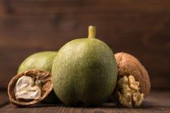 Cosecha fresca de nueces en un fondo de madera Nueces verdes y marrones Shell y cáscara de nueces Fotografía de archivo libre de regalías