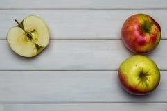 Cosecha madura roja y verde del conjunto y del corte de las manzanas del otoño, desde arriba en la tabla de madera blanca Fotografía de archivo libre de regalías