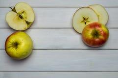 Cosecha madura roja y verde del conjunto y del corte de las manzanas del otoño, desde arriba en la tabla de madera blanca Fotos de archivo