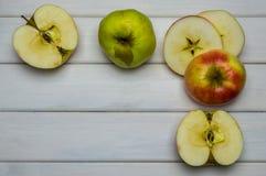 Cosecha madura roja y verde del conjunto y del corte de las manzanas del otoño, desde arriba en la tabla de madera blanca Foto de archivo libre de regalías