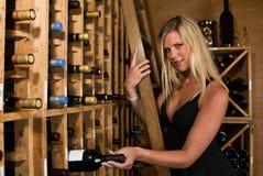 Cosecha rubia hermosa una botella de vino Imágenes de archivo libres de regalías