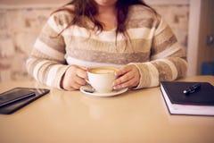 Cosecha sin cabeza de la muchacha rechoncha asentada con un café fresco fotografía de archivo