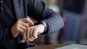 Cosecha tirada del hombre que comprueba tiempo Coseche el tiro del varón usando smartwatch mientras que se sienta en café almacen de metraje de vídeo