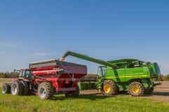 Cosecha y cargamento combinados de la soja en el camión del grano Imagenes de archivo