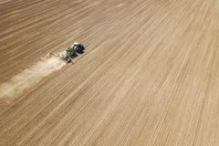 Cosechas aéreas de la siembra del tractor en el campo imagen de archivo