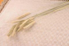 Cosechas del trigo sobre el mantel de lino Imagen de archivo