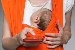 Coseche a la madre con el bebé en la honda que sostiene smartphone imágenes de archivo libres de regalías