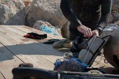 Coseche la opinión el hombre adulto del buceador en una costa con el engranaje spearfishing y el pulpo recién pescado fotos de archivo libres de regalías