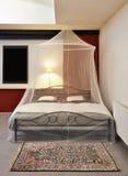 Cosi uitstekend bed met klamboe Royalty-vrije Stock Afbeeldingen