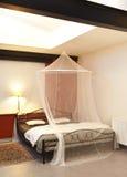 Cosi uitstekend bed met klamboe Stock Afbeelding