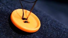 Cosiendo un botón anaranjado en vaqueros, dril de algodón, cierre para arriba metrajes