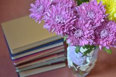 Bouquet of flowers in vase with books nearby stock photos