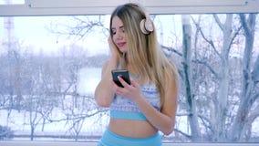Cosiness casero, rubio con el artilugio en las manos que escuchan la música a través de los auriculares en el fondo de la ventana almacen de metraje de vídeo