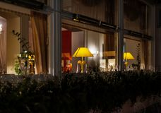 Cosiness restraunt outdoor view at night, with lamps behind the windows royalty free stock photo