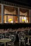 Cosiness restraunt outdoor view at night, with lamps behind the windows stock photography