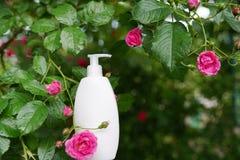 Cosm?tico de la despedregadora Botella blanca en fondo de las flores de la naturaleza con el espacio de la copia Cuidado de la ca imagenes de archivo