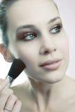 Cosméticos da pele - mulher que usa a escova em sua face Fotografia de Stock