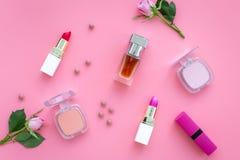 Cosméticos del tono de Rose Barra de labios, bulto, sombreador de ojos entre las flores color de rosa en la opinión superior del  imagen de archivo