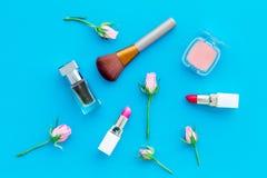 Cosméticos del tono de Rose Barra de labios, bulto, sombreador de ojos, perfume entre las flores color de rosa en la opinión supe fotografía de archivo libre de regalías