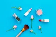 Cosméticos del tono de Rose Barra de labios, bulto, sombreador de ojos, perfume entre las flores color de rosa en la opinión supe foto de archivo
