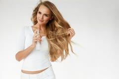 Cosméticos do cabelo Mulher que aplica o pulverizador no cabelo longo bonito imagens de stock royalty free