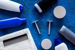 Cosméticos do ` s dos homens para cuidados capilares e rapagem Champô, gel, lâmina, cera no copyspace azul da opinião superior do Fotos de Stock