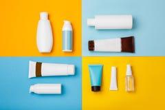 Cosméticos dos cuidados com a pele do verão no fundo amarelo e azul imagens de stock royalty free