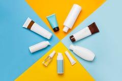Cosméticos dos cuidados com a pele do verão no fundo amarelo e azul foto de stock royalty free