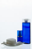 Cosméticos em umas garrafas azuis em um fundo branco Fotografia de Stock