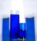 Cosméticos em umas garrafas azuis em um fundo branco Foto de Stock