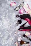Cosméticos en perfume y zapatos en un fondo gris con el espacio de la copia Fotografía de archivo libre de regalías