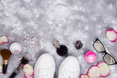 Cosméticos en perfume y zapatos en un fondo gris con el espacio de la copia Imágenes de archivo libres de regalías