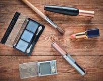 Cosméticos femeninos para la disposición del maquillaje en una tabla de madera Sombras cosméticas, cepillo del maquillaje, lápiz  Foto de archivo
