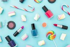 Cosméticos femeninos y caramelo de azúcar brillante en fondo en colores pastel azul Visión superior Endecha plana Escritorio feme Foto de archivo libre de regalías